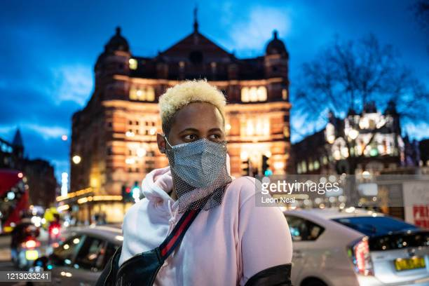 Tourist poses for a photograph in the West End while wearing a decorated surgical mask on March 17, 2020 in London, England. Boris Johnson held the...