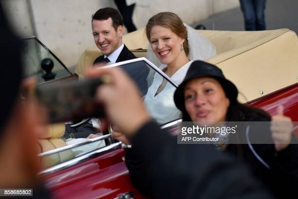 A tourist poses for a picture as Prince Philip of Serbia also known as Filip Karadjordjevic and his bride Danica Marinkovic leave the Belgrade...