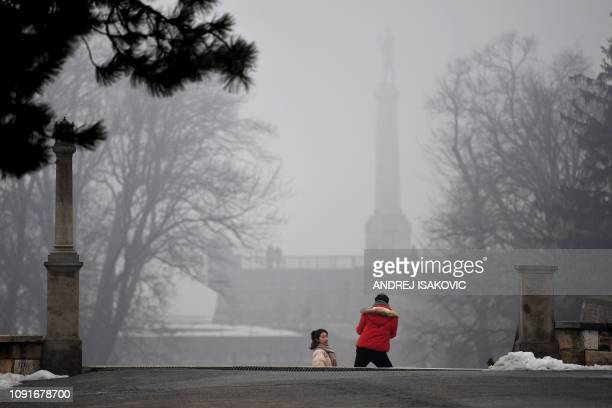 """Tourist poses for a picture near """"The Victor"""" monument in the Upper Town of the Belgrade Fortress, on January 31 as heavy fog and air pollution..."""