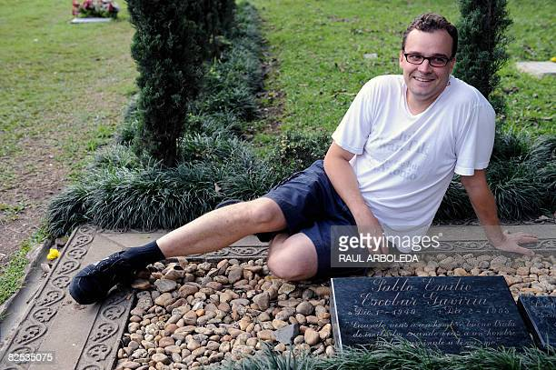 A tourist poses for a picture next to the tombstone of Colombian drug lord Pablo Escobar in Medellin Antioquia department Colombia on August 21 2008...