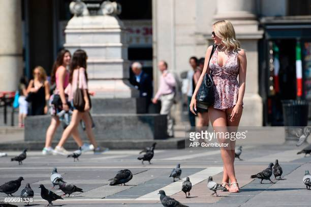 Tourist poses for a picture on June 22, 2017 at Piazza Duomo in Milan on a hot summer-day. In Italy, forecasters say the current heatwave could turn...