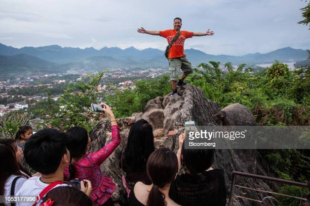 A tourist poses for photographs at Mount Phousi in Luang Prabang Laos on Sunday Oct 21 2018 Laos's economy is set to expand at 7 percent this year...
