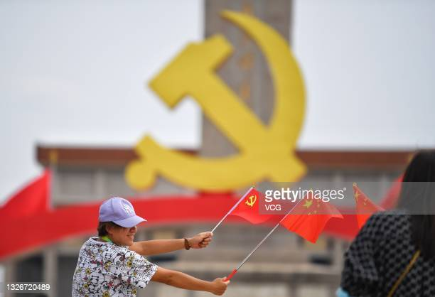 Tourist poses for photos in front of an art installation marking the 100th anniversary of the founding of the Communist Party of China at Tiananmen...