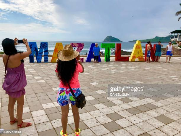 A tourist poses for pictures in Mazatlan Sinaloa state Mexico on October 20 before the arrival of Hurricane Willa Hurricane Willa upgraded to maximum...