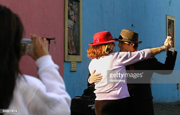 A tourist poses for pictures with a street tango dancer in Caminito the traditional tango district of Buenos Aires Argentina April 15 2006...