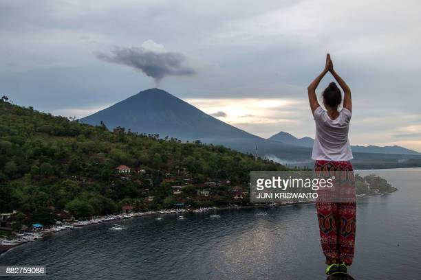 A tourist poses in front of Mount Agung at Amed beach in Karangasem on Indonesia's resort island of Bali on November 30 2017 Thousands of foreign...