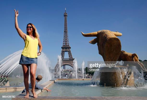 A tourist poses in front of the Eiffel Tower on June 27 2018 in Paris France After two dark years following the terrorist attacks of 2015 the summer...
