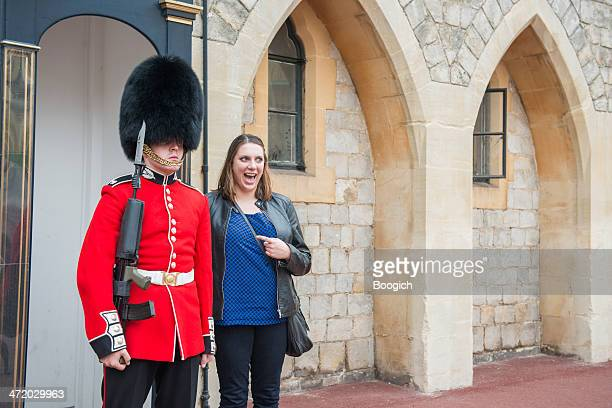 tourist poses with queen's guard at windsor castle - guardsman stock pictures, royalty-free photos & images