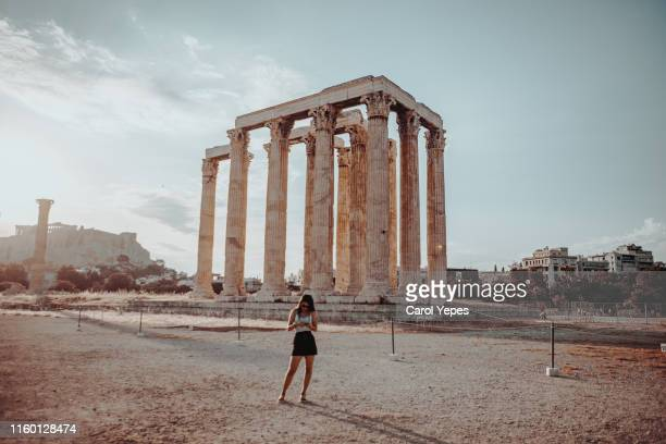 tourist posing in front of temple of olympian zeus in athens, greece - front view photos et images de collection