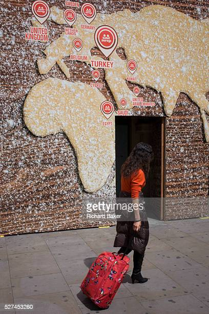 Tourist pulls baggage beneath a world map on a bakery business hoarding The woman passes beneath the large billboard screening off construction work...