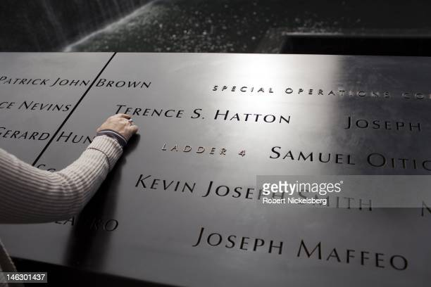 A tourist puts her hand on one of the inscribed names of those who perished in the 911 attacks at the 911 Memorial June 6 2012 in New York City...