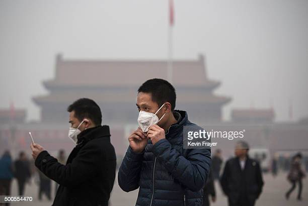 A tourist puts on a face mask to protect against pollution as he visits Tiananmen Square during smog in Tiananmen Square on December 9 2015 in...