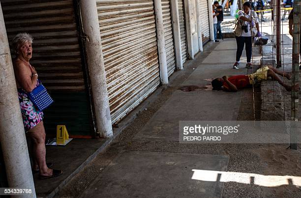 A tourist reacts next to the body of a man murdered in Papagayo beach in the tourist city of Acapulco Guerrero state Mexico on May 25 2016 / AFP /...