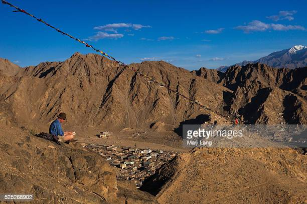 Tourist reading a book at Namgyal Tsemo gompa situated on a mountain top behind the Leh palace the monastery offers panoramic views of the...