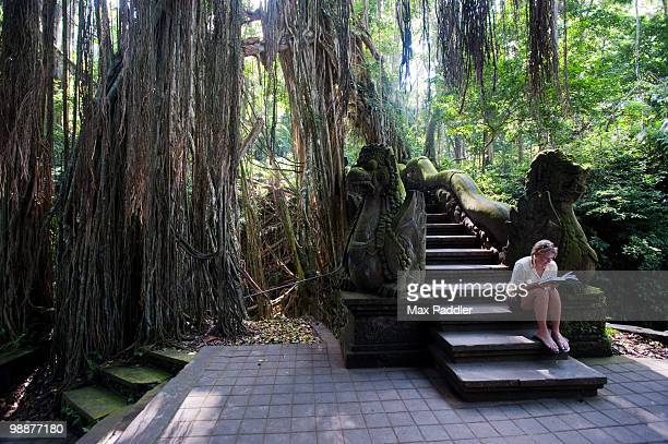A tourist reading a guide book in a monkey forest