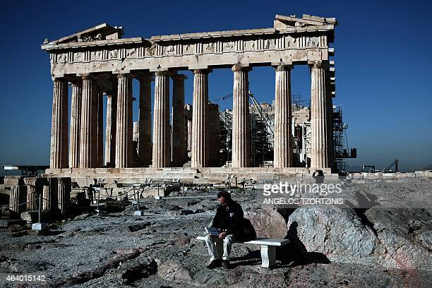 A tourist reads a book in front of the Parthenon Temple at the Acropolis hill in Athens on February 21 2015 Greece's radical left government was at...