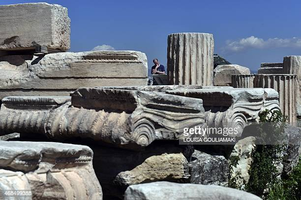 A tourist reads information while visiting the ancient Acropolis in Athens on April 3 2015 Thousands of tourists visit Athens on the easter holiday...