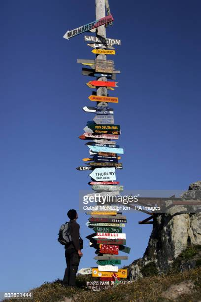 A tourist reads place signs nailed to a telegraph pole on the outskirts of Stanley Falkland Islands Almost 4 million pounds is generated by tourists...
