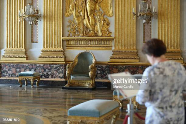 A tourist reads the guide inside the throne salon in the royal apartments inside the Royal Palace of Caserta