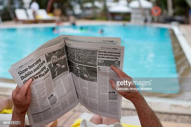 A tourist reads the Irish Independent newspaper at a Puerto del Carmen hotel swimming pool on April 13 2014 in Lanzarote Spain Lanzarote where...