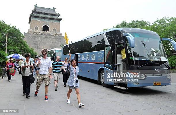 A tourist rejects the offer from a vendor of buying fake watches as travellers follow their tour guide during a visit to central Beijing's ancient...