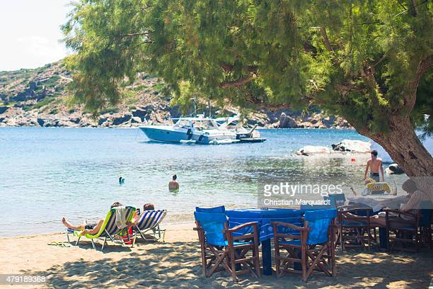 Tourist relax under a tree on the beach during midday next to the town of Faros on June 19 2015 in Sifnos Greece Sifnos is a island in the western...