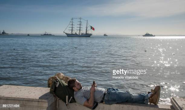 A tourist relaxes by the Tagus River while Portuguese and foreign ships lay at anchor during the commemoration day of the Portuguese Navy's 700th...