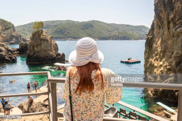 tourist relaxing by la grotta beach with rock formations in paleokastritsa, corfu, kerkira, greece - corfu stock pictures, royalty-free photos & images