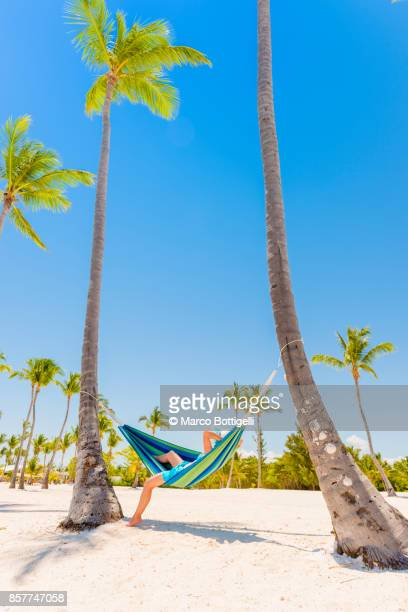 tourist relaxing on a hammock on a tropical beach - punta cana fotografías e imágenes de stock