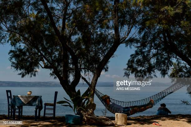 A tourist rests on a hammock on a beach near the village of Skala Sykamineas in the northeastern island of Lesbos on August 3 2018