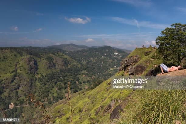 A tourist rests on a rock on Little Adam's Peak with a steep drop below, Ella, Sri Lanka