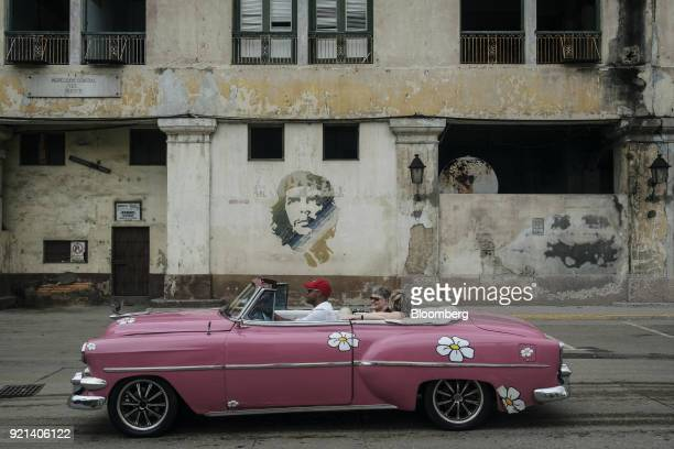 Tourist ride in a vintage American car while passing in front of graffiti displaying the image of former Revolutionary leader Ernesto 'Che' Guevera...