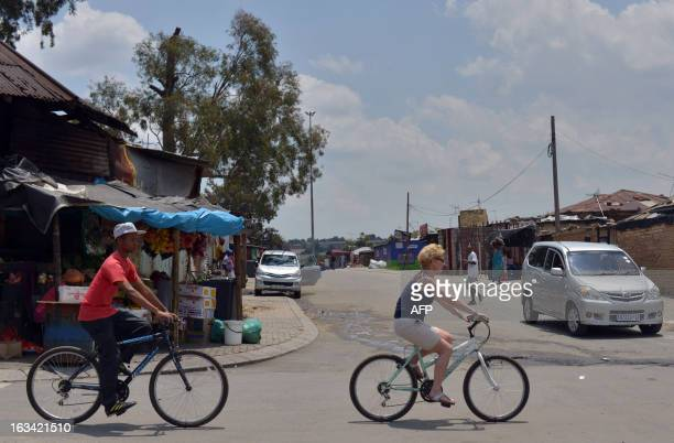 A tourist rides a bicycle in Alexandra township Johannesburg on February 12 2013 Muludzi Tours offers the opportunity to discover one of the oldest...