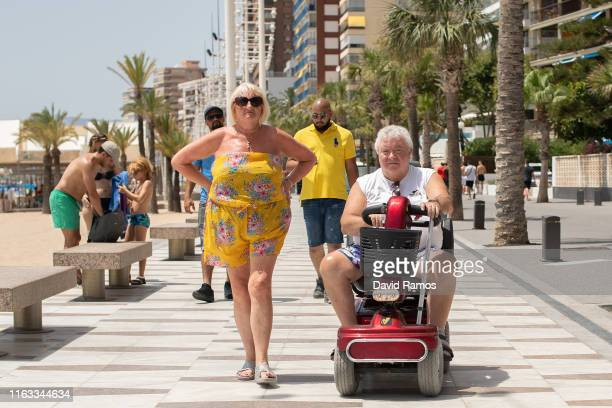 A tourist riding a mobility scooter drives along Levante Beach on July 21 2019 in Benidorm Spain More than 39 million of tourists are expected to...