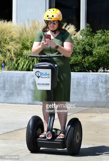 Tourist riding a Segway PT personal transporter uses her smartphone during a stop on a guided Segway tour in Nashville, Tennessee.