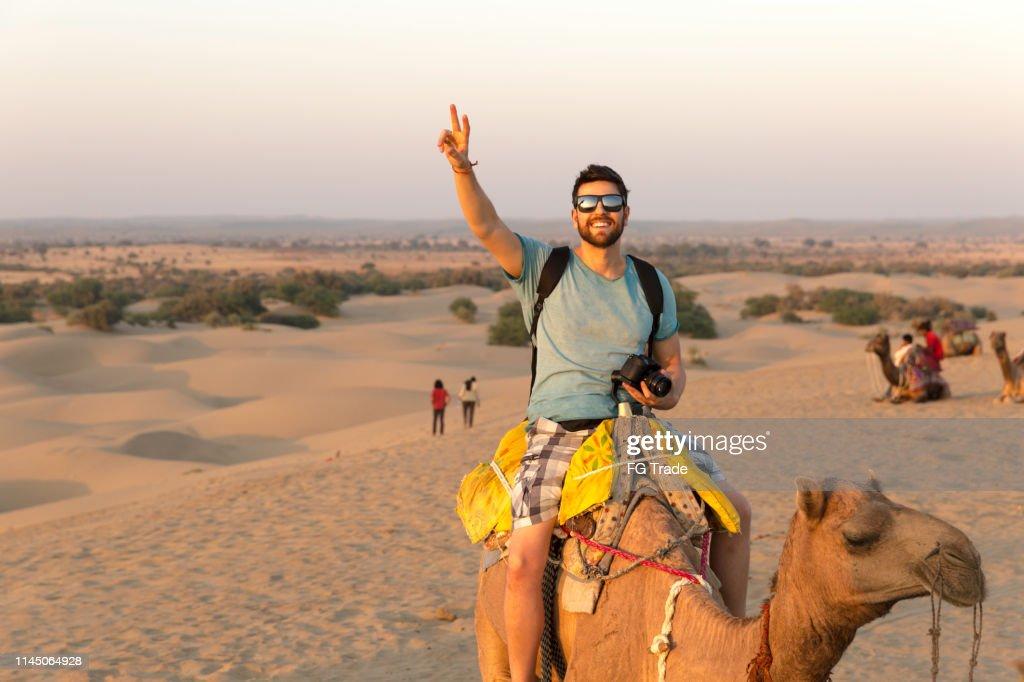 Tourist riding camel in Desert : Stock Photo