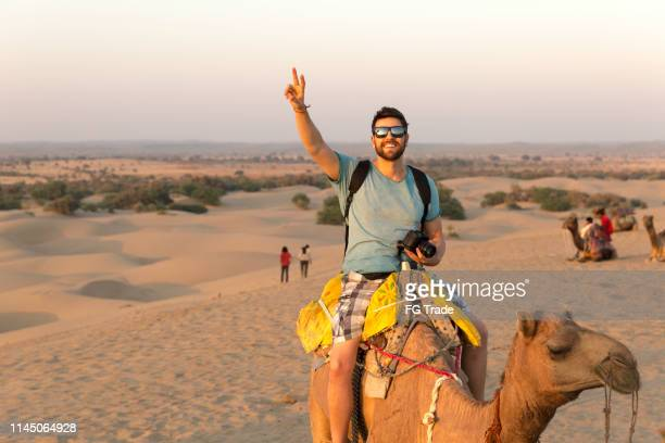 tourist riding camel in desert - tourism stock pictures, royalty-free photos & images