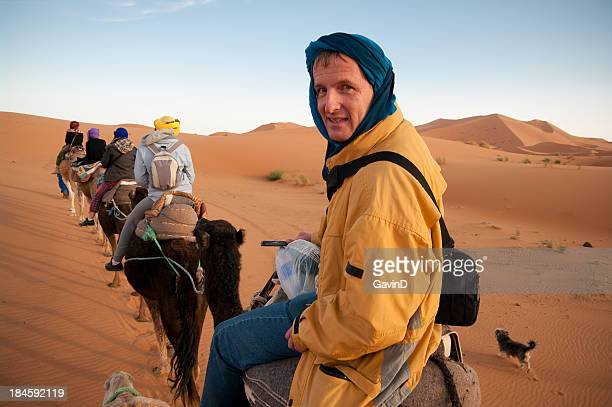 Tourist riding camel train in Sahara Desert, Africa