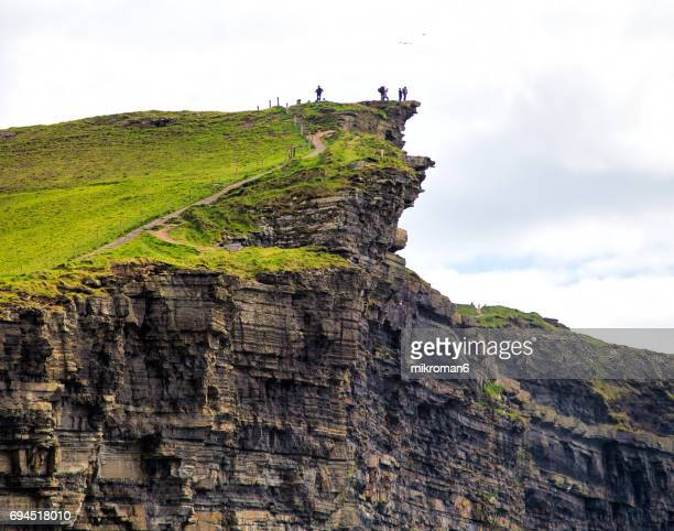 Tourist risk their lives approaching to the very edge of Cliff of Moher, Ireland
