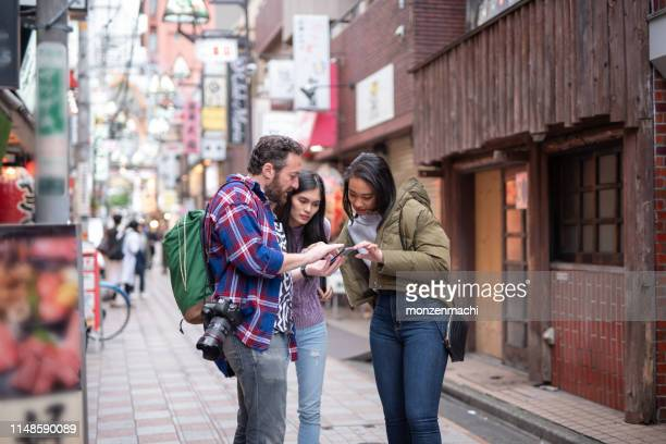 tourist searching way to go with smart phone - tourist stock pictures, royalty-free photos & images