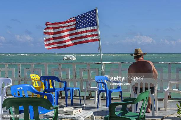 A tourist seats next to an american flag is seen at Bavaro Beach El Cortecito on December 30 2016 in Punta Cana Dominican Republic