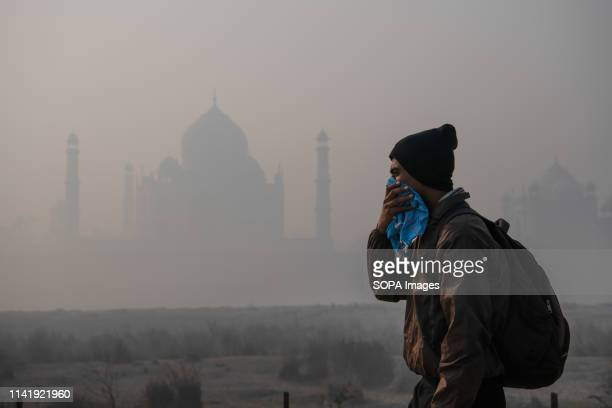 Tourist seen covering his face striving to guard himself from immense pollution in front of Taj Mahal, which is half concealed in smoke. Air...