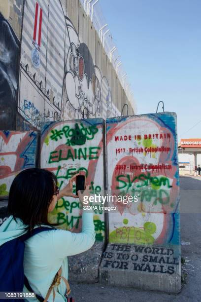 A tourist seen taking a picture of graffiti on the West Bank Separation Wall The Israeli Separation Wall is a dividing barrier that separates the...