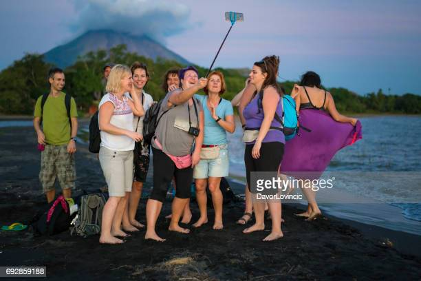 Tourist selphie on Island Ometepe in Lake Nicaragua with volcano in background, Nicaragua