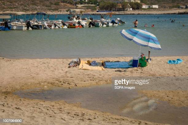 A tourist shelters under an umbrella at Stavros beach which is located on the northern side of Akrotiri in Crete Island
