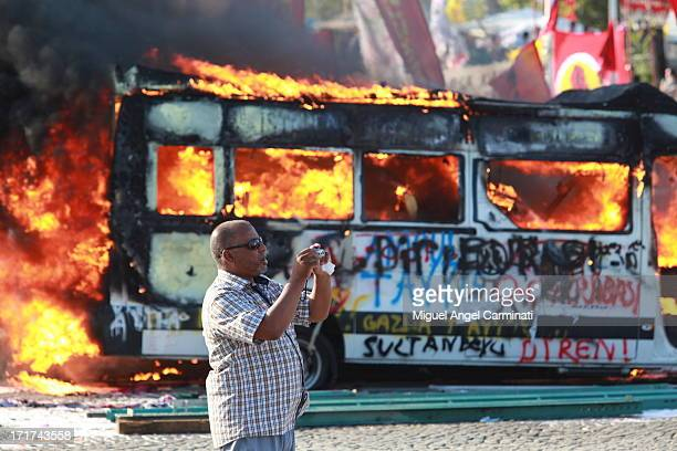 CONTENT] A tourist shoots pictures in Taksim Square in front of a vehicle in flames after the riots following the violent eviction of Gezi Park