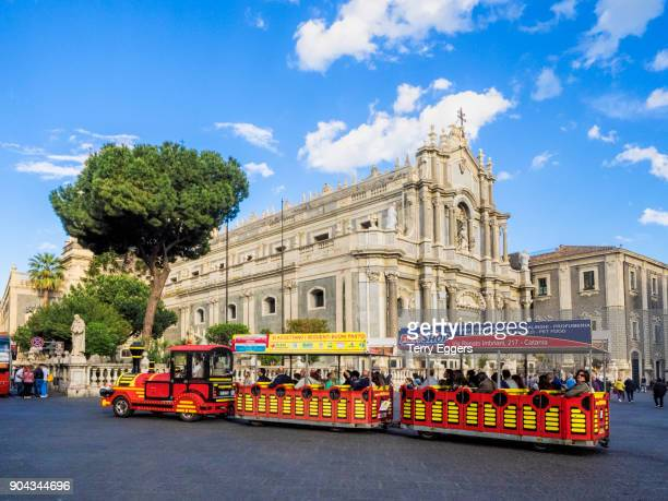 Tourist shuttle train and view of Piazza del Duomo and Catania cathedral from Garibaldi street, Catania, Sicily, Italy.
