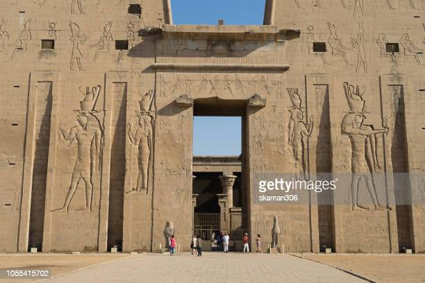 edfu, egypt - october 06: tourist sigh seeing ruin stone carving god horus and osiris at edfu temple near nile river unesco site  october, 2018 in edfu, egypt - tomb of ramses iii stock pictures, royalty-free photos & images