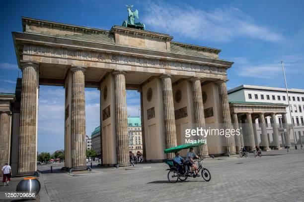 Tourist sightseeing bike past Brandenburg Gate during the novel coronavirus pandemic on June 19, 2020 in Berlin, Germany. Travel restrictions...