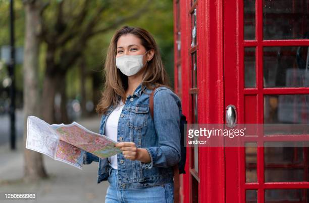 tourist sightseeing in london during the covid-19 outbreak wearing a facemask while holding a map - tourist stock pictures, royalty-free photos & images